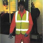 mannequin-man performming as a Living and Real Mannequin: mannequin man at the Arco experience alexandra palace 1997, wearing an orange boilersuit and hi-viz jacket for Arco on 10/09/1997