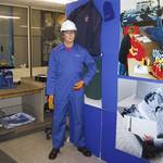mannequin-man performming as a Living Mannequin: mannequin man set up in embroidery display area, wearing blue overall with embroidered name and white hard hat for Arco on 24/05/2000