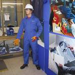 Mannequin man performing as a living safety dummy at an Open Day at Arco East Anglia, Bury St. Edmunds. Pictures in the embroidery display area wearing blue overall with embroidered name; in the shop area wearing a red overall, hi-vis waistcoat and white hard hat; and in the loading bay wearing a red overall and BA kit (breathing apparatus)