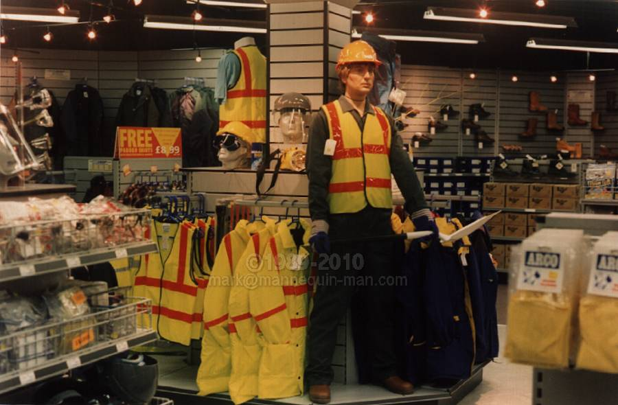 mannequin on centre display holding spade, wearing green overall, yellow hi-vis vest and hard hat. Living mannequin in Arco Orpington shop
