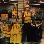 Mannequin man the human mannequin performing as a living safety dummy at the Arco shop in orpington wearing green overall and orange hard hat
