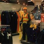mannequin-man performming as a Living Mannequin: mannequin on centre display holding spade, wearing green overall, yellow hi-vis vest and hard hat for Arco on 29/10/1994
