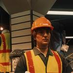 mannequin-man performming as a Living Mannequin: mannequin on centre display wearing green overall, yellow hi-vis vest and hard hat for Arco on 29/10/1994