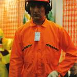 mannequin-man performming as a Living Mannequin: Mannequin man the human mannequin performing as a living safety shop mannequin at the Arco Experience in Edinburgh dressed in a bright orange coverall with price tag and hard hat with ear defenders for Arco on 13/09/1995