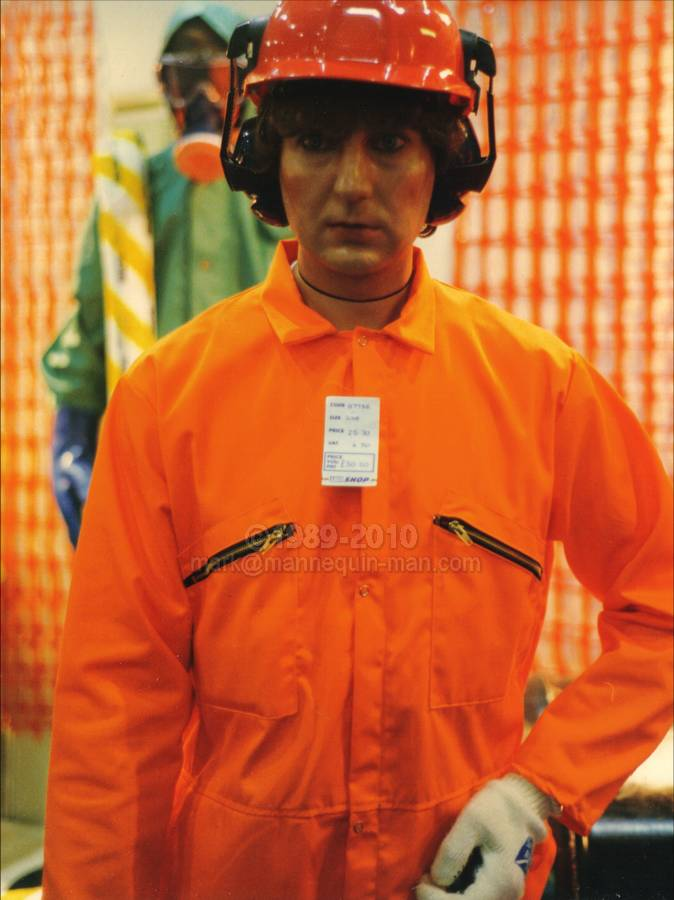 Mannequin man the human mannequin performing as a living safety shop mannequin at the Arco Experience in Edinburgh dressed in a bright orange coverall with price tag and hard hat with ear defenders - Living Mannequin Arco Experience Royal Highland Showground, Ingliston, Edinburgh