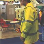 mannequin-man performming as a Living Mannequin: mannequin man on Arco stand at RoSPA wearing an orange Trojan coverall, and yellow hi-vis jacket for Arco on 21/05/1996