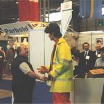 mannequin-man performming as a Living Mannequin: mannequin man on Arco stand at RoSPA surprising a passer by, wearing an orange Trojan coverall, and yellow hi-vis jacket for Arco on 21/05/1996