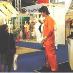 mannequin-man performming as a Living Mannequin: mannequin man on Arco stand at RoSPA wearing an orange Trojan coverall for Arco on 21/05/1996