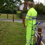 Mannequin dressed in yellow hi-vis coverall tied to trolley outside arrow safety