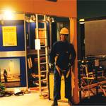 mannequin-man performming as a Living Mannequin: mannequin man on BH-SALA stand at RoSPA, wearing blue overall, yellow hard hat and yellow BH-SALA safety harness for BH Sala on 21/06/1995