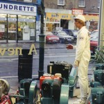 mannequin-man performming as a Living Mannequin: mannequin man in Clarkes Power Tool Shop window wearing white Clarkes overall with white cap for Clarke International on 14/02/1991