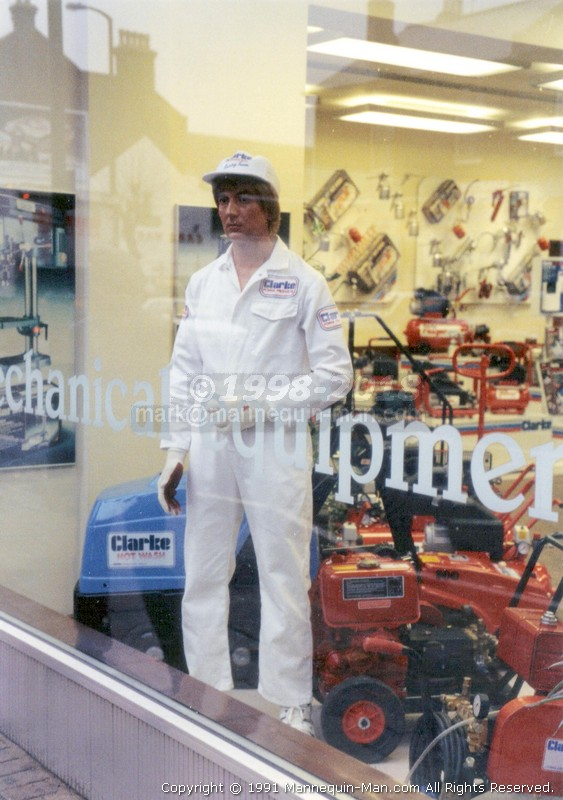 mannequin man in Clarkes Power Tool Shop window wearing white Clarkes overall with white cap - Living Mannequin Clarke Shop Hommerton, Hackney,London