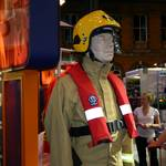 mannequin-man performming as a Living Mannequin: mannequin man standing on Cosalt Ballycare stand at Fire 2004 dressed in a Frontier fire coverall,secifically designed for use in wildland fire situations, this lightweight one-piece coverall aims to reduce the risk of heat exhaustion due to physical exertion over long distances for Cosalt on 07/09/2004