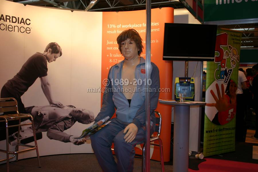 Mannequin-man in his role as danny CPR, the world's most lifelike cpr training dummy demoing a Defibrillator on the Cardiac Science Stand at the Education Show, NEC 2010 - Realistic danny-CPR Dummy Education Show NEC