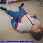 mannequin-man performming as a CPR Dummy: danny cpr mannequin being used in basic life support course, Danny cpr shown wearing a one-peice red/white/blue joggingsuit overall, also avaiable in a red fire resistant overall for West Mids Fire Service on 28/03/2003