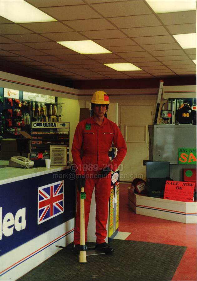 Living Mannequin wearing red Boilersuit, yellow hard hat, holding pick, placed by trade counter in Crownlea hire shop. Living Mannequin Shop dummy Walthamstow