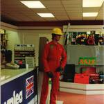 mannequin-man performming as a Living Mannequin: mannequin man with pick axe, with price tags wearing red overall and yellow hard hat in Crownlea Hire shop Walthamstow for Crownlea on 21/10/1995