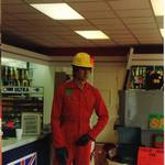 mannequin-man performming as a Living Mannequin: living shop mannequin with pick axe, with price tags wearing red overall and yellow hard hat in Crownlea Hire shop Walthamstow for Crownlea on 21/10/1995