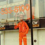 mannequin-man performming as a Living Mannequin: mannequin man as a shop display dummy for Charles Wilson Hire shops in Stratford London 1990. Kitted out in orange overall, orange hi-vis vest, orange gloves and an orange hard hat. for Charles Wilson Hire on 01/01/1990