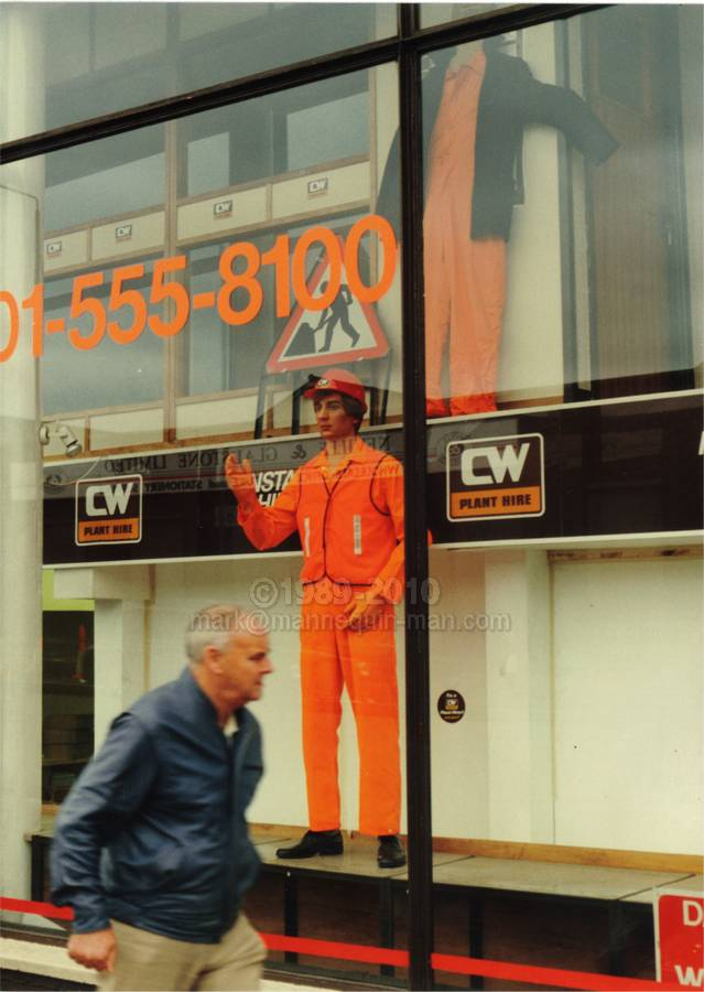 mannequin man as a shop display dummy at Charles Wilson Hire shops in Stratford London 1990. Kitted out in orange overall, orange hi-vis vest, orange gloves and an orange hard hat. - Living Mannequin CW Hire Shop Stratford, London