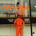 mannequin-man performming as a Living Mannequin: mannequin man working as a window display dummy at Charles Wilson Hire shops in Stratford London 1990. Kitted out in orange overall, orange hi-vis vest, orange gloves and an orange hard hat. for Charles Wilson Hire on 01/01/1990