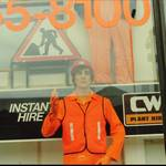mannequin-man performming as a Living Mannequin: mannequin man working as a window display dummy for Charles Wilson Hire shops in Stratford London 1990. Kitted out in orange overall, orange hi-vis vest, orange gloves and an orange hard hat. for Charles Wilson Hire on 01/01/1990