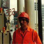mannequin-man performming as a Living Mannequin: mannequin man working as a shop display dummy at Charles Wilson Hire shops in Stratford London 1990. Kitted out in orange overall, orange hi-vis vest, orange gloves and an orange hard hat. for Charles Wilson Hire on 01/01/1990