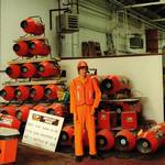 mannequin-man performming as a Living Mannequin: mannequin man as a shop display dummy at Charles Wilson Hire shops in Stratford London 1990. Kitted out in orange overall, orange hi-vis vest, orange gloves and an orange hard hat. for Charles Wilson Hire on 01/01/1990