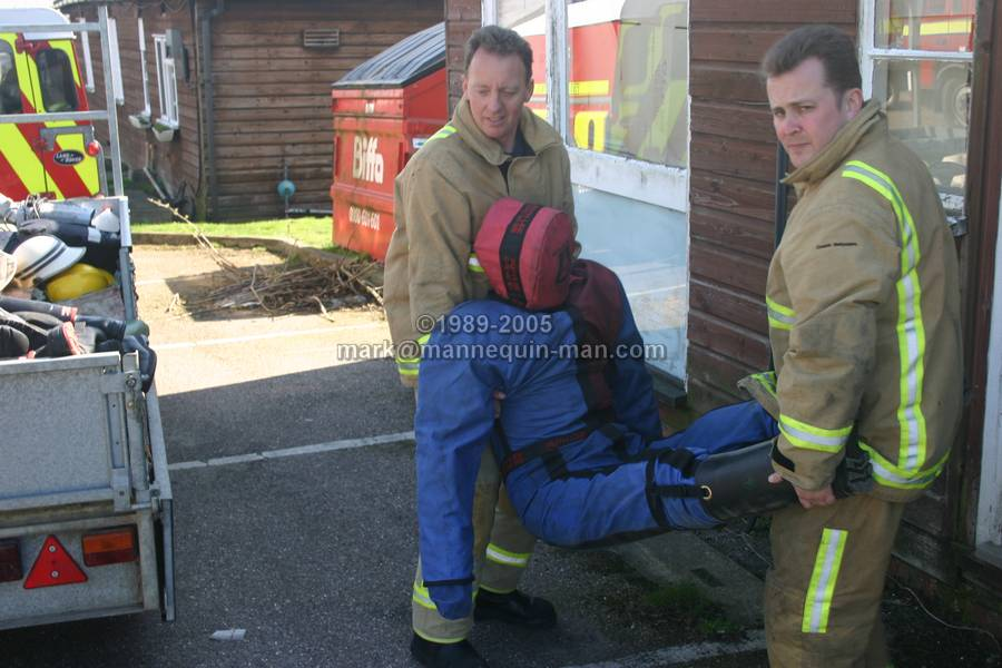 living ruthlee drag drill dummy being caried by fire-fighters at Event Fire & Rescue, Redhill Aerodrome - living drag dummy being caried by fire-fighters