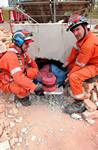 mannequin-man performming as a drag dummy: After drilling a hole through the rubble, two members of the UKFS SAR team pull the 'live' drill drag dummy maniken casualty out though the hole during the EAZ demonstration at the International Fire Expo 2005.  for Firex (CMP Information) on 17/05/2005