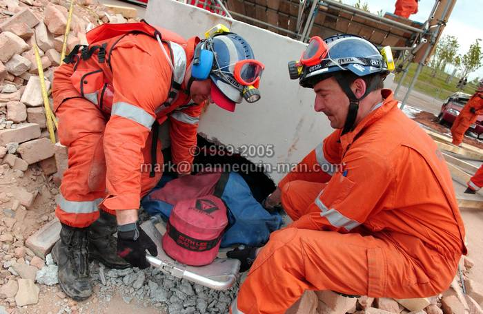 After drilling a hole through the rubble, two members of the UKFS SAR team pull the 'live' drill drag dummy casualty out though the hole during the EAZ demonstration at the International Fire Expo 2005. - UKFS SAR team pull the 'live' drill drag dummy casualty out though the hole