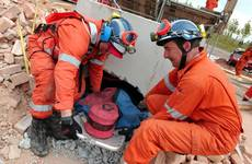 mannequin-man performming as a drag dummy: After drilling a hole through the rubble, two members of the UKFS SAR team pull the 'live' drill drag dummy casualty out though the hole during the EAZ demonstration at the International Fire Expo 2005. for Firex (CMP Information) on 17/05/2005