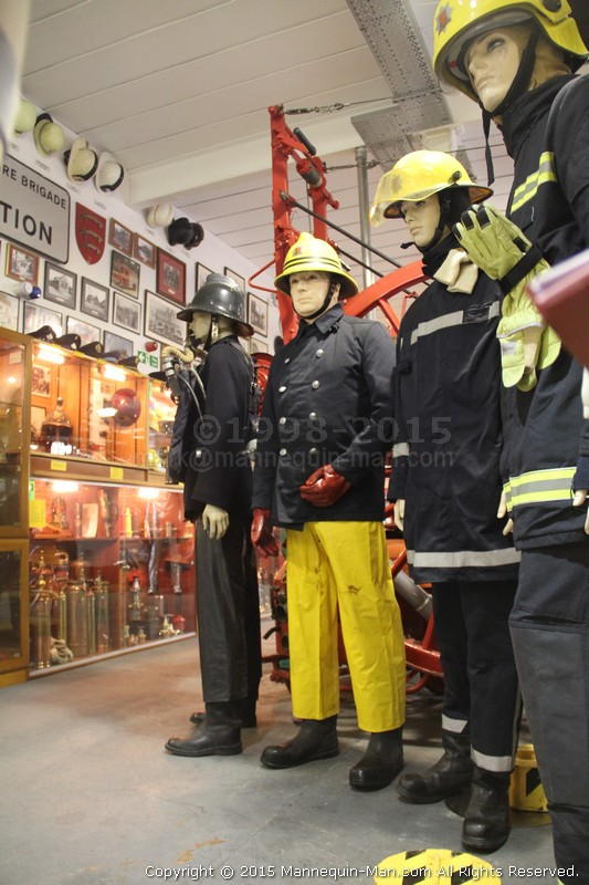Taking the place of a mannequin wearing a 1970s fireman's uniform during a Family Fun Day at the Essex Fire museum to the amusement of the visiting children - Firefighter Uniform Exhibit at the Essex Fire Museum