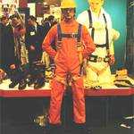 mannequin-man performming as a Living Mannequin: mannequin man on Greenham Trading stand at RoSPA wearing orange overall, yellow hard hat and blue/yellow safety harness for Greenham Trading on 20/06/1995