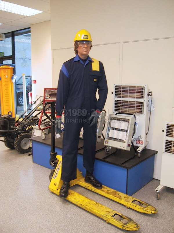 Mannequin man standing in the HSS Hire Shop at Kings Cross wearing blue HSS overalls and a yellow hard hat