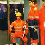 Display piece with three mannequins/dummies, mannequin man wearing orange hi-vis overall and yellow hard hat, other real mannequins wearing hi-vis wet weather gear, taken at the Career and Workwear show for Faithful Ltd, who manufacture industrial and safety clothing