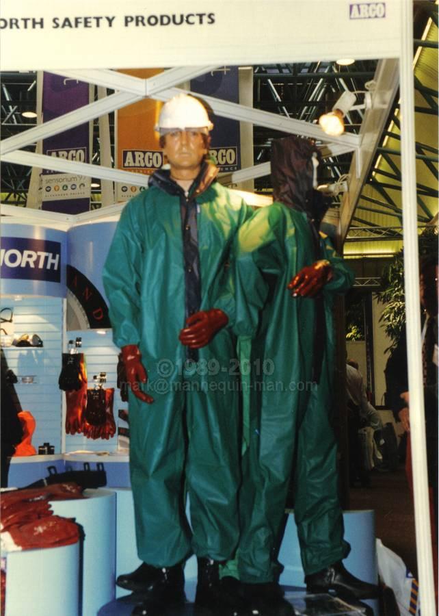 mannequin man working as a living display dummy wearing a PREMIER Green/blue lightweight PVC coated nylon fabric boilersuit, standing on podium with real manneqiuins wearing similar chemical protective clothing on the North Safety Stand at an Arco Experience. Living Mannequin Arco Experience Alexandra Palace, London