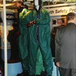 mannequin-man performming as a Living and Real Mannequin: mannequin man working as a living display dummy wearing a PREMIER Green/blue lightweight PVC coated nylon fabric boilersuit, standing on podium with real manneqiuins wearing similar chemical protective clothing on the North Safety Stand at an Arco Experience stand wearing green chemical resistant overall, white hard hat and red PVC gloves for North Safety Products on 11/09/1997