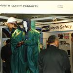 mannequin-man performming as a Living and Real Mannequin: mannequin man working as a living display dummy wearing a PREMIER Green/blue lightweight PVC coated nylon fabric boilersuit, standing on podium with real manneqiuins wearing similar chemical protective clothing on the North Safety Stand at an Arco Experience for North Safety Products on 11/09/1997
