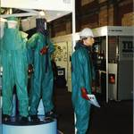 mannequin-man performming as a Living and Real Mannequin: mannequin man working as a living display dummy wearing a PREMIER Green/blue lightweight PVC coated nylon fabric boilersuit, holding a catalogue on the North Safety Stand at an Arco Experience for North Safety Products on 11/09/1997