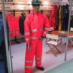 mannequin-man performming as a Living Mannequin: mannequin man standing on ocean rainwear stand wearing a hi-vis red waterproof coverall at the safety & health expo 2002 for Ocean Rainwear on 14/05/2002