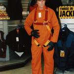Mannequin man the human mannequin performing as a living safety dummy at the Arco shop in orpington wearing Yellow hi-vis overall with orange hard hat and Orange overall with fall arrest harness