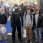 mannequin-man performming as a Living Mannequin: Mannequin man wearing a Magic Marine Regatta Drysuit standing with some fans on the LDC Sailing Parts & Clothing stand at the RYA Dinghy Show Alexandra Palace 2013 for LDC Sailing Parts & Clothing on 02/03/2013