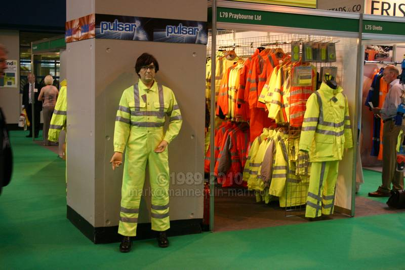 performing as a human show dummy on the stand of Praybourne Limited wearing a yellow pulsar teflon coated coverall - Living Mannequin Safety & Health Expo NEC