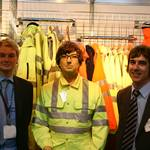 mannequin-man performming as a Living Mannequin: performing as a human show dummy on the stand of Praybourne Limited wearing a yellow pulsar teflon coated coverall posing with Praybourne employees for Praybourne on 13/05/2008
