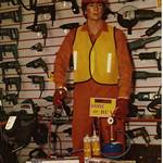 mannequin-man performming as a Living Mannequin: mannequin man demonstrating equipment in shop, wearing orange overall and hard hat and yellow his-vis jacket for SBN on 02/01/1990