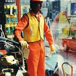 mannequin-man performming as a Living Mannequin: living mannequin man in shop window display wearing orange overall and hardhat and yellow his-vis jacket being watched by two children for SBN on 02/01/1990