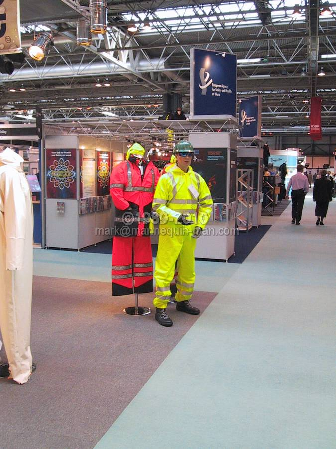 mannequin man standing on sioen stand wearing a hi-vis yellow waterproof coverall at the safety & health expo 2002 - Living Mannequin Safety & Health Expo NEC