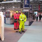 mannequin man standing on sioen stand wearing a hi-vis yellow waterproof coverall at the safety & health expo 2002
