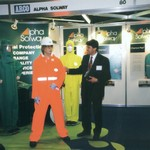 mannequin-man performming as a Living and Real Mannequin: Wearing a High Visibility (Hi-Vis) Orange Chemsol Plus Chemical protective clothing coverall suit and white hard hat being inspected by a customer for Alpha Solway on 17/09/1998